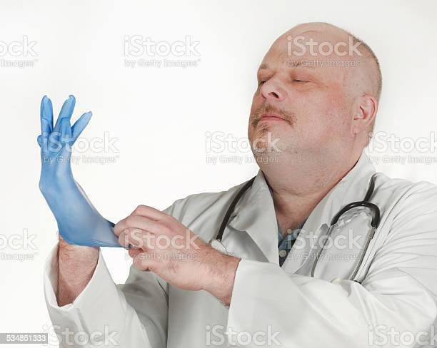 serious-doctor-pulling-on-a-rubber-glove